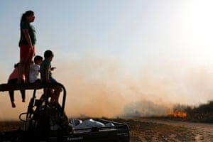 Be'eri, IsraelIsraeli children watch a field burning at their kibbutz. It was set alight by a kite carrying a molotov cocktail launched by Palestinian protesters in Gaza.
