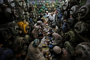 Mechanics eat iftar, the evening meal at the end of the day's fast during Ramadan, in Delhi, India