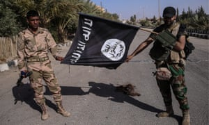 Syrian Arab Army soldiers hold a seized Islamic State flag in Palmyra, Syria, 2016.