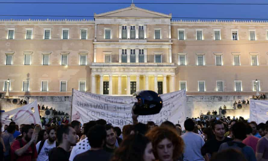 Riot police stand on the steps of the Athens parliament building, as leftist protesters hold an anti-EU demonstration on Sunday.