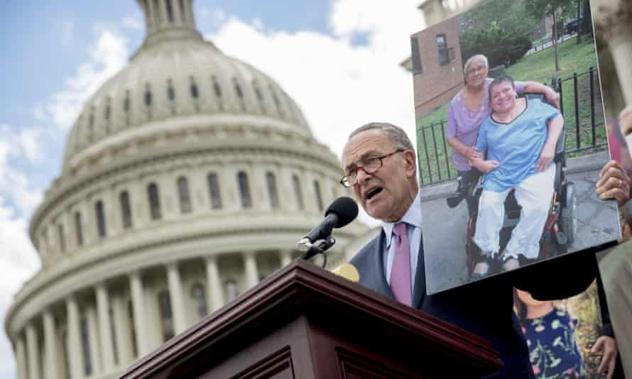 Senate minority leader Chuck Schumer holds up a photograph of constituents who would be adversely affected by the proposed Republican bill.