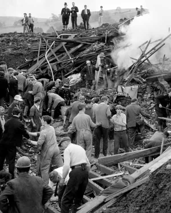 Rescue workers remove mud and rubble burying one of a row of seven houses at Aberfan in 1966.