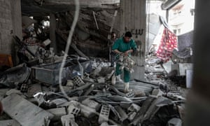 A man sifts throught the ruins of a hospital on the outskirts of Damascus after the building was heavily damaged by an air strike