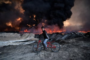 A boy pauses as he cycles past an oilfield set on fire by retreating Isis fighters in Qayyarah, Iraq