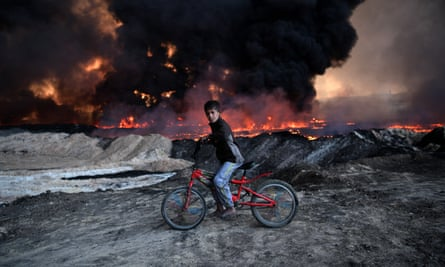 A boy pauses on his bike as he passes an oil field that was set on fire by retreating ISIS fighters ahead of the Mosul offensive, on October 21, 2016