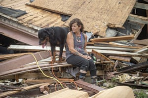A woman and her dog Dave sit outside a home destroyed by Hurricane Ida in Houma, La.