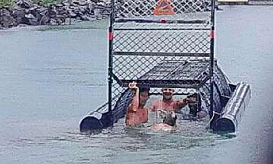 Facebook photo showing a group of men swimming into a baited crocodile trap near the site of a recent fatal attack.