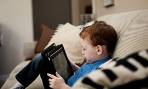 Small boy sitting on sofa looking at a tablet