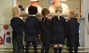 Infant school children queuing for school lunch
