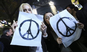 People in Tokyo show solidarity with victims of Paris terrorist attacks, with the Eiffel Tower peace symbol designed by Jean Jullien.