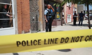Police investigate a crime scene after two people were shot on street in Chicago's West side in June.