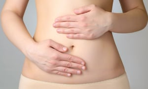 A woman holds her stomach