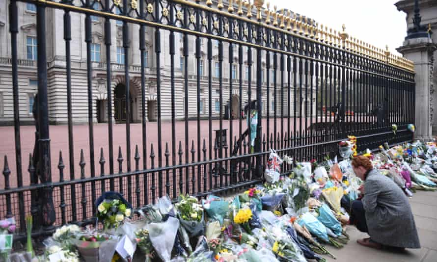People place flowers with condolence messages outside Buckingham Palace