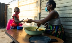 Samantha Murozoki (R) hands a free meal to a young neighbour at her home in Chitungwiza on May 5, 2020, where she feeds people struggling during the coronavirus lockdown in Zimbabwe. -With the help of volunteers Murozoki serves over a 100 hot meals per day