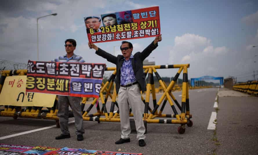 Anti-North Korea protesters hold banners at a checkpoint on the Unification Bridge between the two countries.