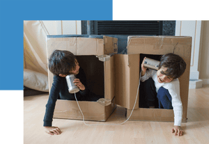 Two boys in cardboard boxes playing with can and string phones