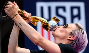 Megan Rapinoe, centre, lifts the Women's World Cup alongside her US teammates at a parade in New York. The US have won the tournament four times.