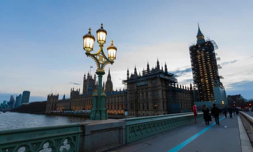 People walk along Westminster Bridge past the Houses of Parliament and Big Ben