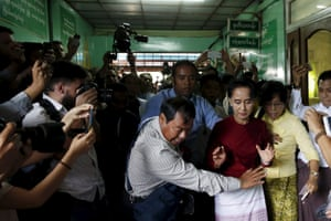 Myanmar's opposition NLD party leader Aung San Suu Kyi reacts when some cameramen fall to the floor before casting her ballot in Yangon