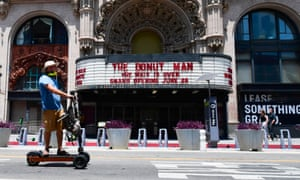 A man rides a scooter past the facade of the Million Dollar Theater announcing the opening of a donut shop in Los Angeles.