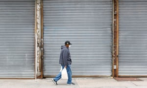 A man walks past shuttered businesses in the Bronx, New York, last week.