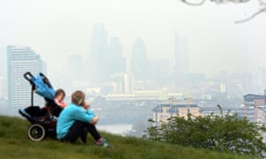 Picture of woman and baby in Greenwich park, the City of London obscured by pollution.