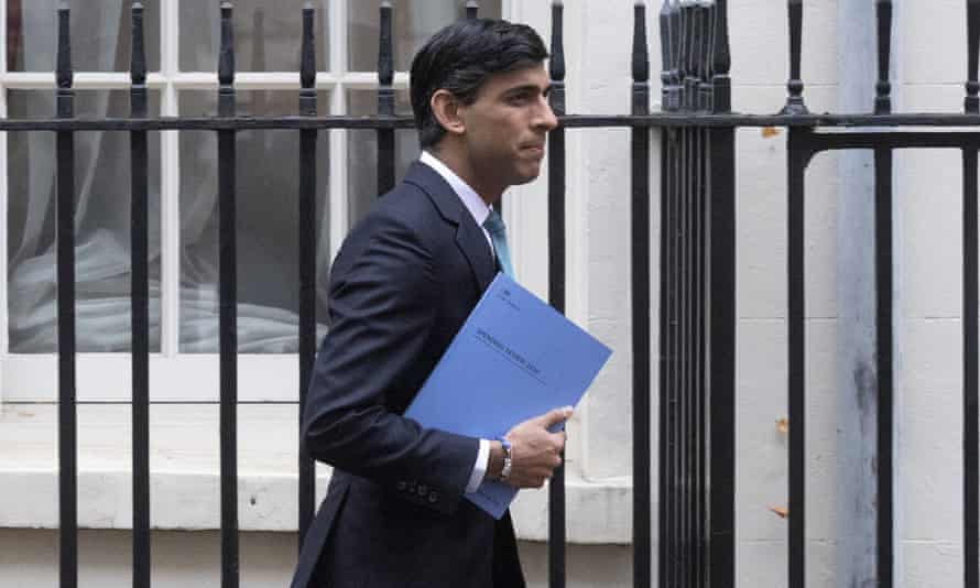 Risahi Sunak in a suit walking past a line of black railings, holding his 2020 spending review, which has a pale blue cover, under his arm