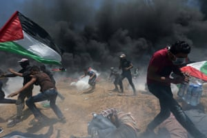 Palestinian demonstrators flee from Israeli fire and teargas