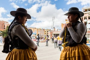 Estela Loyaza, 22, right, talks with A Quispe, a cholita colleague, before they start their shift as traffic wardens in El Alto