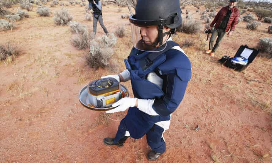 A member of Japan Aerospace Exploration Agency (JAXA) retrieves the first samples of asteroid subsurface, dropped by Hayabusa2 in Woomera
