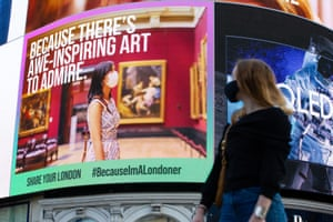 London, UK. A woman looks at a digital billboard at Piccadilly Circus promoting the #BecauseImALondoner campaign