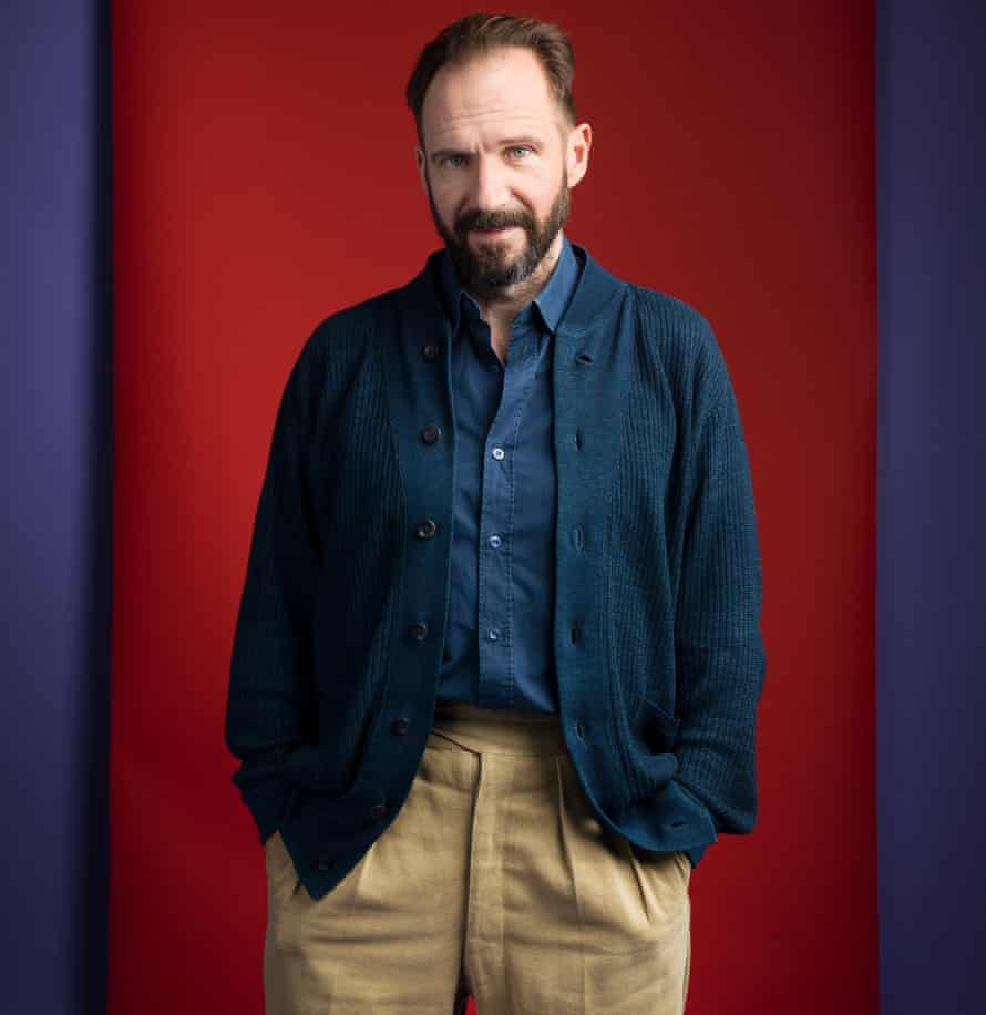 Ralph Fiennes with a beard in a shirt and cardigan, hands in his trouser pockets