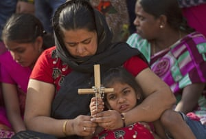 A mother and daughter pray as they watch a re-enaction of the crucifixion in Hyderabad, India
