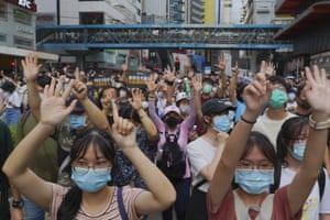 Protesters gesture with five fingers, signifying their five key demands of the government