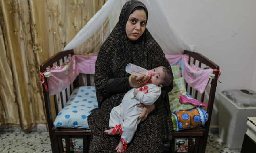 Hiba Swailam, 24, carrying her five-month-old baby in Beit Lahia.