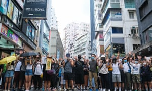 Demonstrators with hand gestures gather on the street during a banned protest in Hong Kong