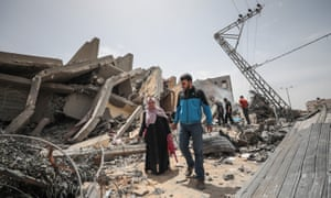 Palestinians search their usable wares from collapsed buildings after Israeli warplanes carried out airstrikes in Gaza City, Gaza on May 06, 2019