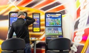 Man using a fixed-odds betting terminal in a betting shop.