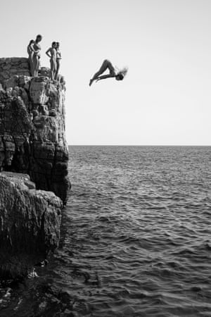 Girl Power, a black & white photograph recording the moment when a woman dives off a cliff on the island of Lokrum near Dubrovnik, Croatia, while her friends stand-by and watch