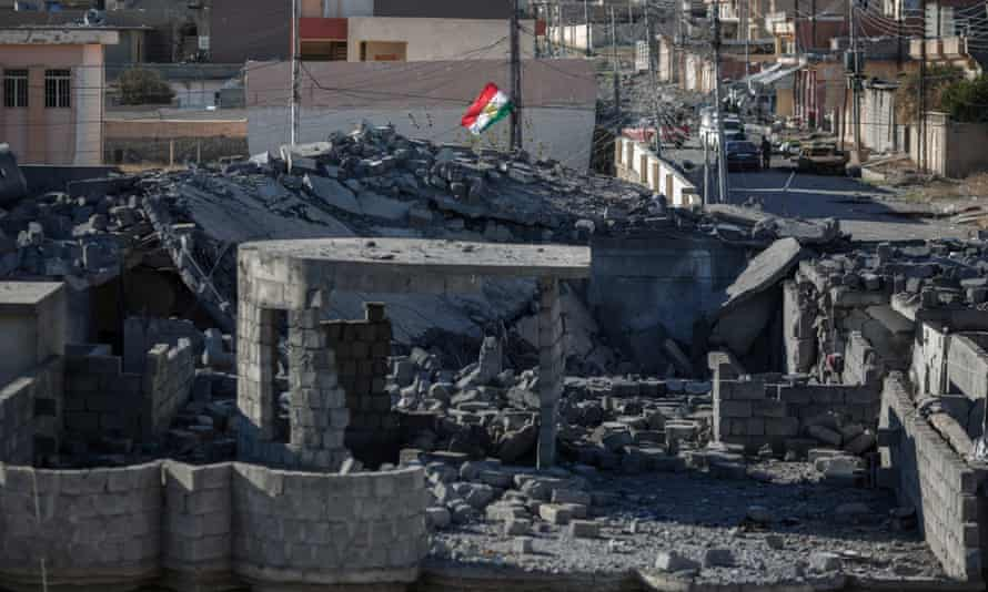The flag of the Kurdish regional government flies above a house that has been bombed in Sinjar, Iraq.