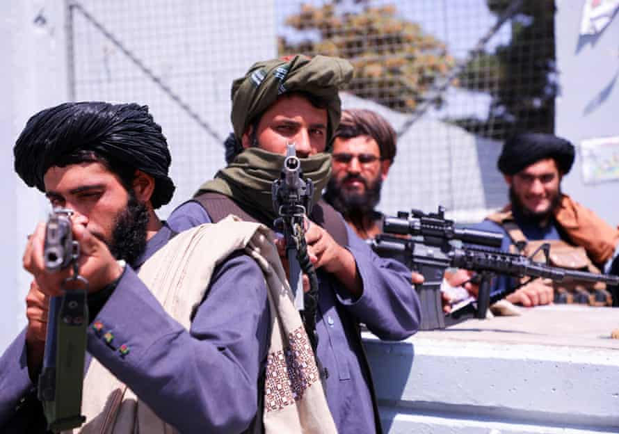 Taliban forces stand guard in front of Hamid Karzai International Airport in Kabul after taking control.