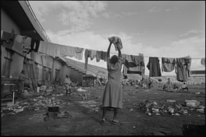 """The Amahoro Stadium, Kigali. During the genocide the stadium was temporarily a """"UN Protected Site"""" hosting up to 12,000 mainly Tutsis refugees. A woman hangs her washing as shelling and killing continued outside the stadium walls."""