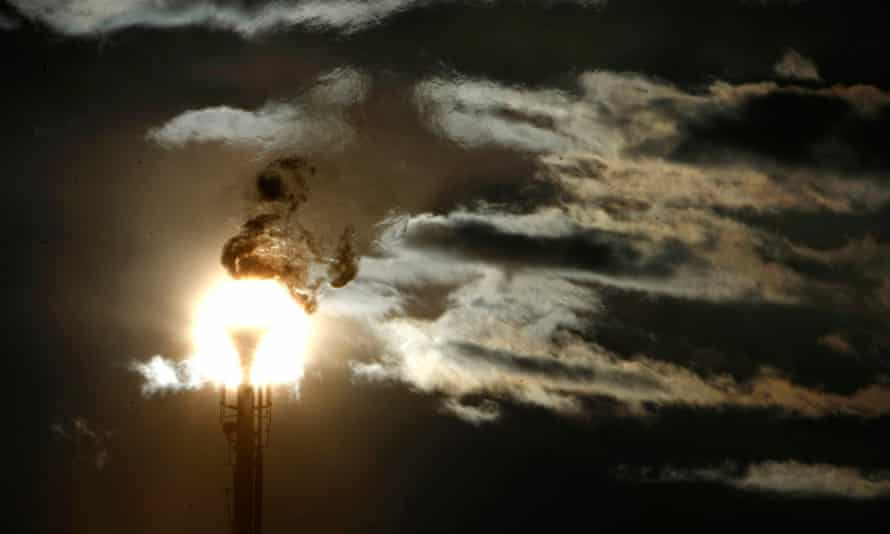 A flare stack emitting fire is silhouetted against the sun at an oil refinery in Melbourne