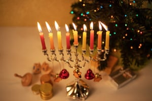 Hanukkah and Christmas together: Hanukkah menorah decorated with bells and stars of David with candles burning alongside Christmas tree