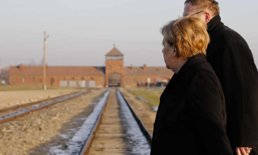Merkel crosses the rail tracks at Auschwitz-Birkenau