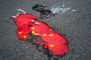 A Chinese flag lies burnt on a street