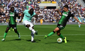 Inter's Romelu Lukaku shoots to score despite the attentions of Sassuolo's Federico Peluso.