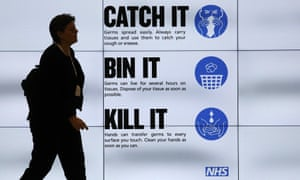 An NHS 'Catch it, bin it, kill it' sign on TV screens in London.