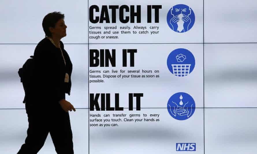 An NHS 'Catch it, bin it, kill it' sign on TV screens in London.