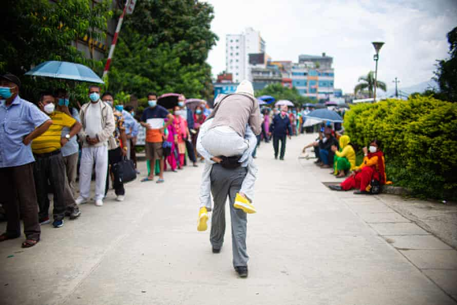 A man carries his father on his back past a queue of people in Kathmandu, Nepal